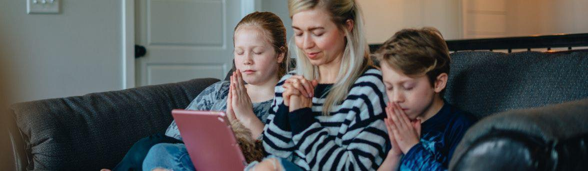 three children looking at a computer and praying