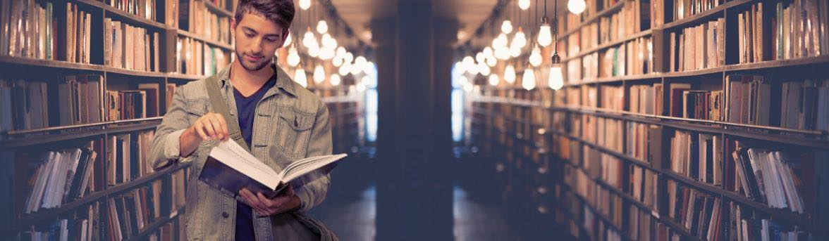 Picture of a man in a library reading a book